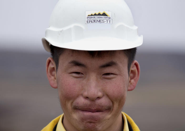In this July 6, 2012 photo, a Mongolian miner smiles while working at Erdenes Tavan Tolgoi, a Mongolian state-owned coal mining company in Tavan Tolgoi, southern Mongolia. Chinese demand for copper and especially coal has propelled the Mongolian economy to one of the world's fastest growing, making some wealthy and driving down poverty in a still poor country, and China wants a larger share of the resources. (AP Photo/Andy Wong)