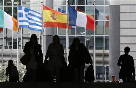 Pedestrians walk towards the Irish, Greek, Spanish and French national flags outside the European Parliament in Brussels