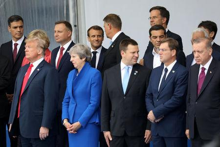 U.S. President Donald Trump, Britain's Prime Minister Theresa May, Estonia's Prime Minister Juri Ratas, Slovenia's Prime Minister Miro Cerar, Turkey's President Tayyip Erdogan, Spain's Prime Minister Pedro Sanchez, Poland's President Andrzej Duda, French President Emmanuel Macron, Romania's President Klaus Werner Iohannis, Netherlands' Prime Minister Mark Rutte and Greek Prime Minister Alexis Tsipras pose for a family picture ahead of the opening ceremony of the NATO (North Atlantic Treaty Organization) summit, at the NATO headquarters in Brussels, Belgium, July 11, 2018.  Ludovic Marin/Pool via REUTERS