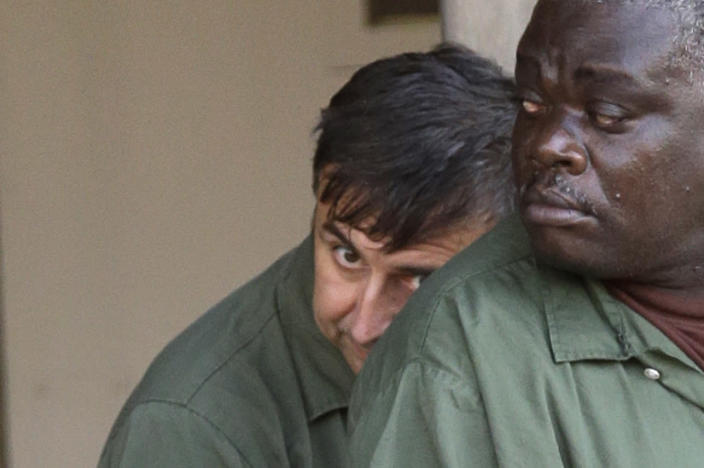 Alexander Fishenko, left, owner of Arc Electronics Inc., hides behind another inmate as they are escorted from the federal courthouse in Houston in 2012. (Photo: David J. Phillip/AP)