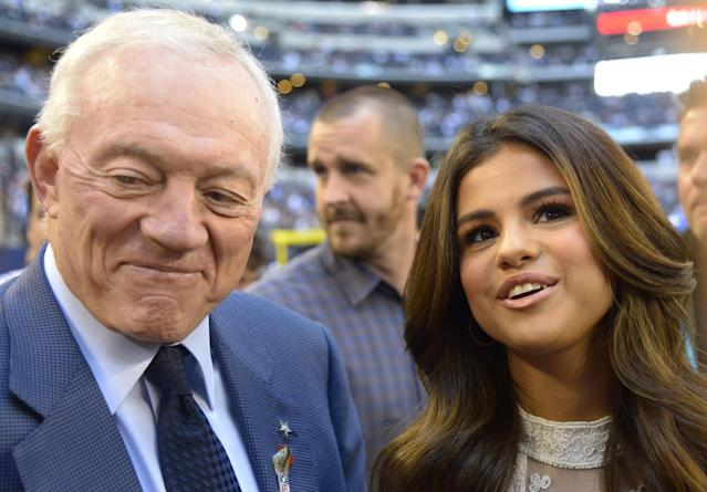 Dallas Cowboys team owner Jerry Jones gives a television interview with entertainer Selena Gomez, right, on the field before an NFL football game against the Minnesota Vikings, Sunday, Nov. 3, 2013, in Arlington, Texas. Gomez will be the half time entertainment on Thanksgiving Day when the Cowboys take on the Oakland Raiders. (AP Photo/Tim Sharp)