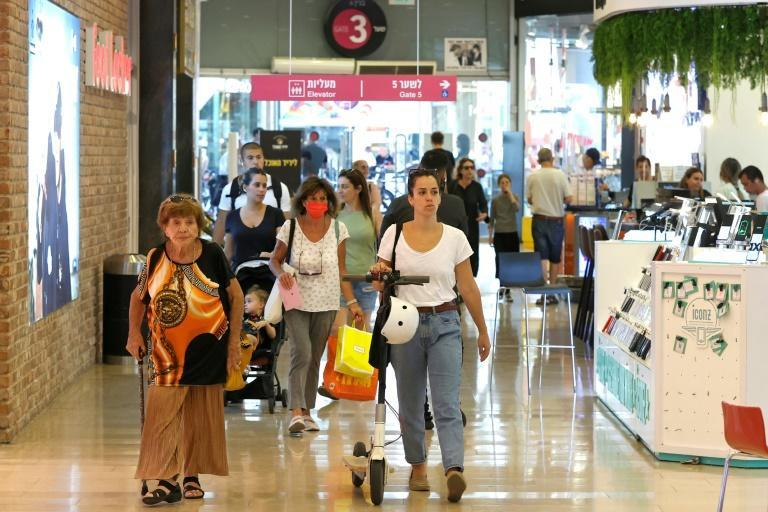 Shoppers in Tel Aviv take advantage of Israel's brief lifting of the requirement for masks to be worn in enclosed public places before it was reimposed on Friday
