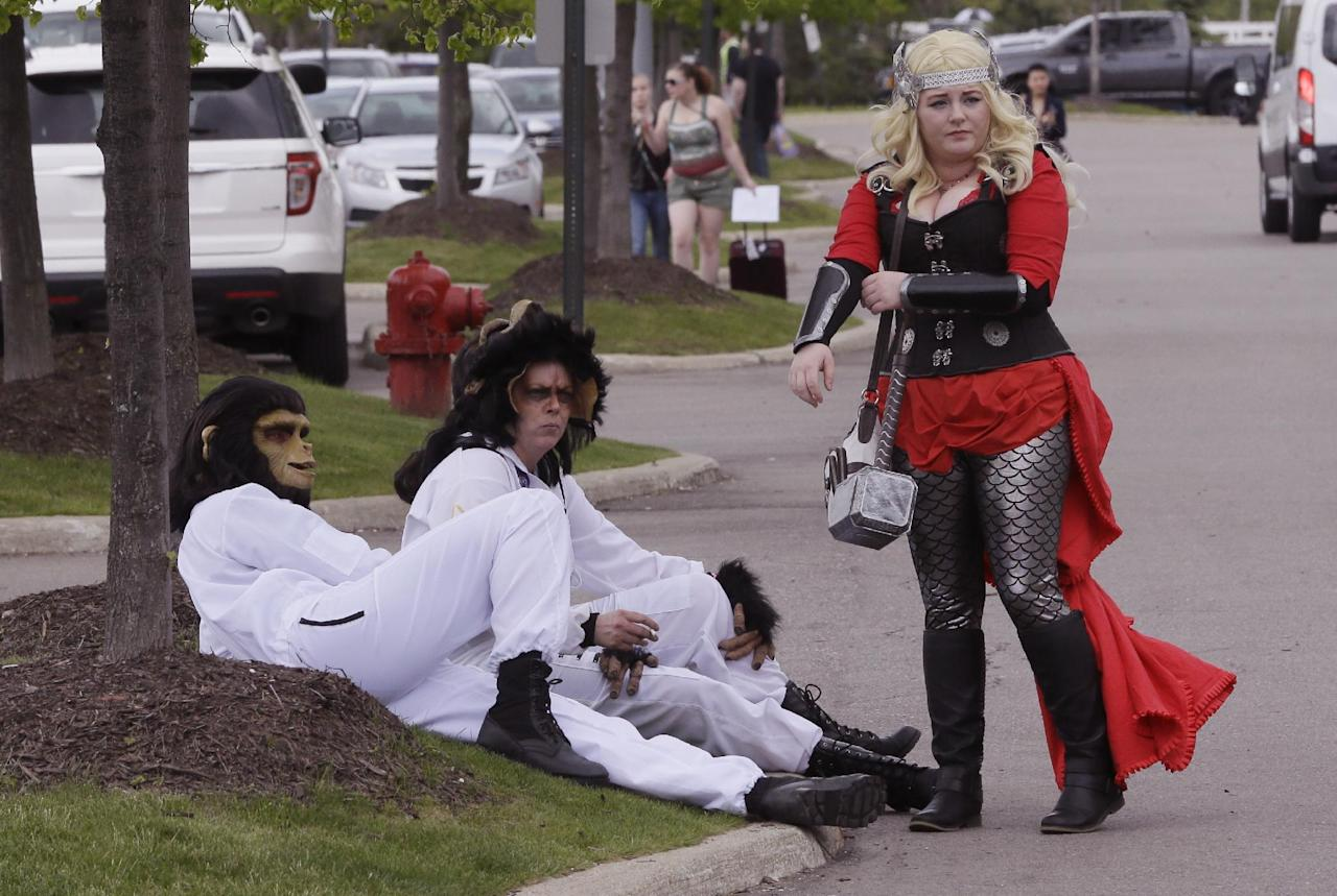 From left, Sean Baumgartner as Cornelius and Rhonda Payne as Caesar from Planet of the Apes, and Katey Griffin as Thor, take a break outside the Motor City Comic Con, Friday, May 13, 2016 in Novi, Mich. Tens of thousands of fans are expected at the 27th annual convention which got underway Friday. The three-day pop-culture extravaganza welcomes dozens of celebrities from TV and film as well as hundreds of comic book creators, writers and artists. (AP Photo/Carlos Osorio)