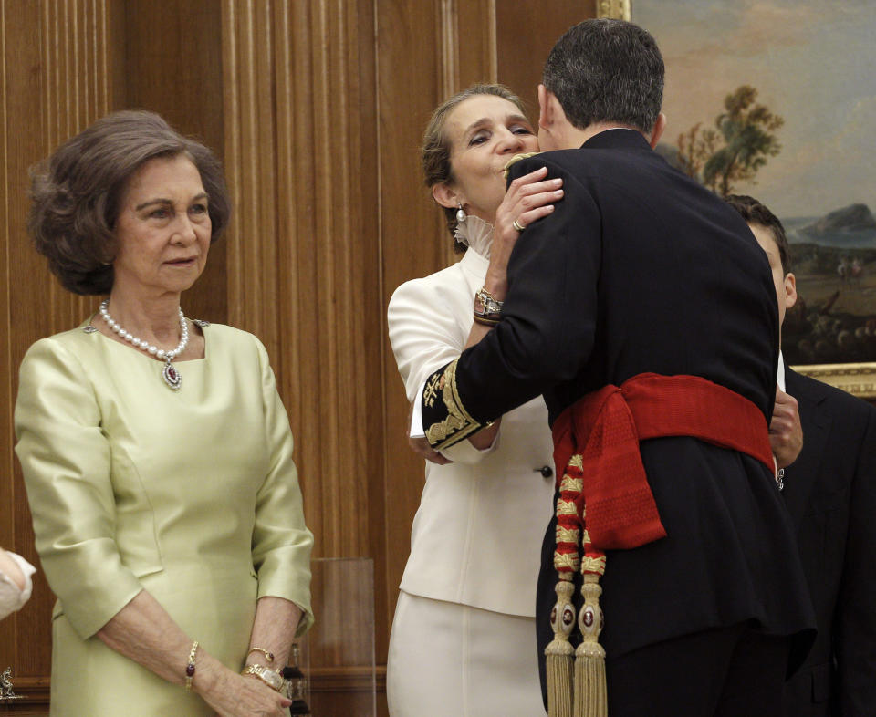Spain's new King Felipe VI (R), wearing the Sash of Captain-General, kisses Infanta Elena next to his mother Queen Sofia (L) during a ceremony at La Zarzuela Palace in Madrid, June 19, 2014. Spain's new king, Felipe VI, will be sworn in on Thursday in a low-key ceremony which monarchists hope will usher in a new era of popularity for the troubled royal household.      REUTERS/Zipi/Pool (SPAIN  - Tags: ROYALS POLITICS ENTERTAINMENT)