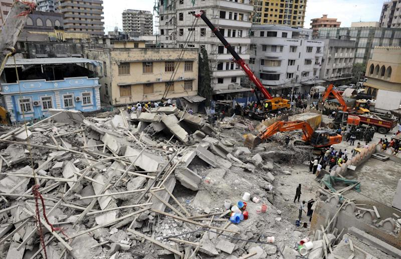 Rescuers using mechanical diggers remove rubble from the site of a collapsed building in downtown Dar es Salaam, Tanzania Friday, March 29, 2013. A Tanzanian police official says the multi-storey building was in the final stages of its construction and most of the people caught up in the collapse were passing by. (AP Photo/Khalfan Said)