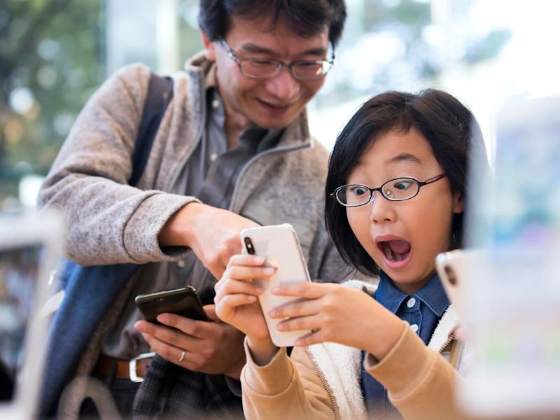 A girl reacts as she tries an iPhone X at the Apple Omotesando store on November 3, 2017 in Tokyo: Tomohiro Ohsumi/Getty Images