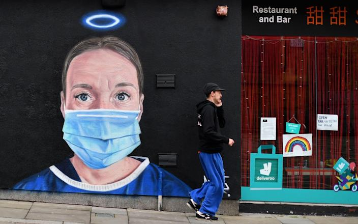 A pedestrian walks past street art depicting a nurse in scrubs and a face mask in Manchester. GPs are angry that NHS England rules will force them to treat patients who refuse to wear face coverings - Paul Ellis/AFP