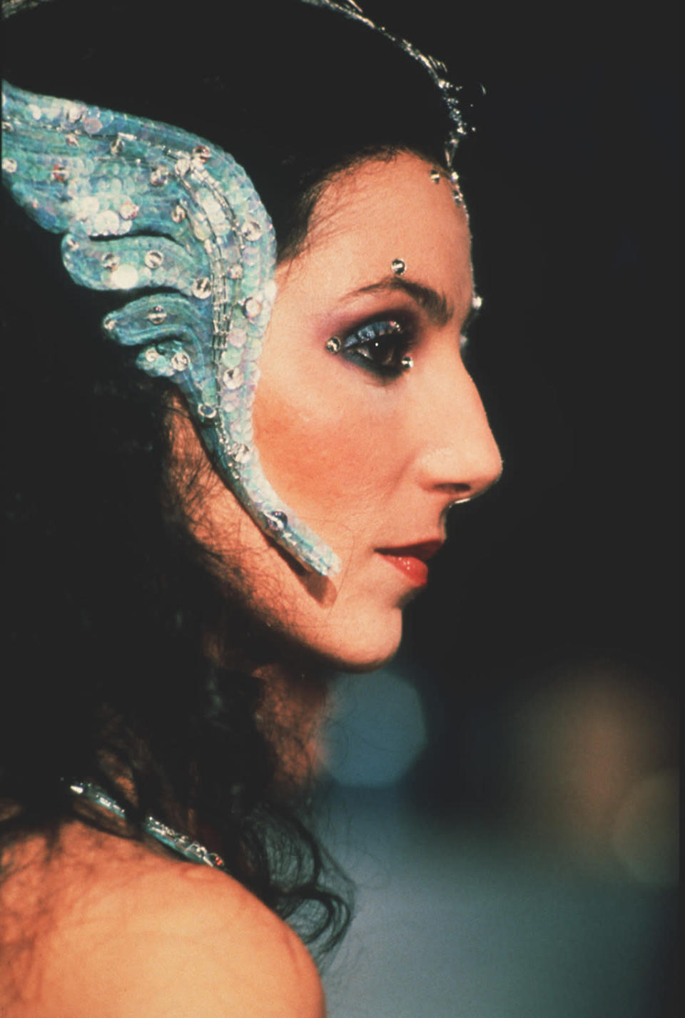 <p>Over-the-top looks started early — here, in 1976, with turquoise lids, matching sequined wings, and a jeweled forehead. <i>(Photo: MPTV Images)</i></p>