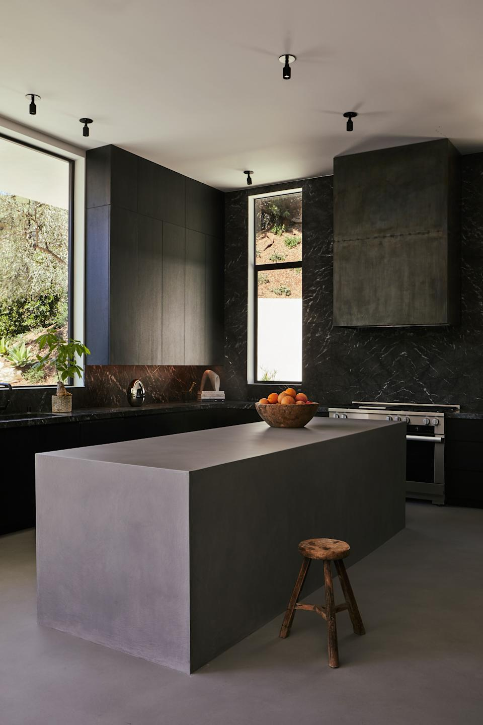 In the kitchen of a midcentury-inspired Hollywood Hills home designed by OSKLO, the blackened steel hood was custom-made, the countertops in honed negro d'Alba are from Stoneland, the spun fiber table lamp was purchased in Morocco, and the American Folk stool is from the 1930s. The knotted burl bowl on the custom concrete finished island was bought in Japan.