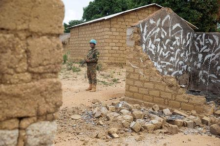FILE PHOTO: A Bangladeshi United Nations peacekeeping soldier stands among houses destroyed by violence in September, in the abandoned village of Yade, Central African Republic