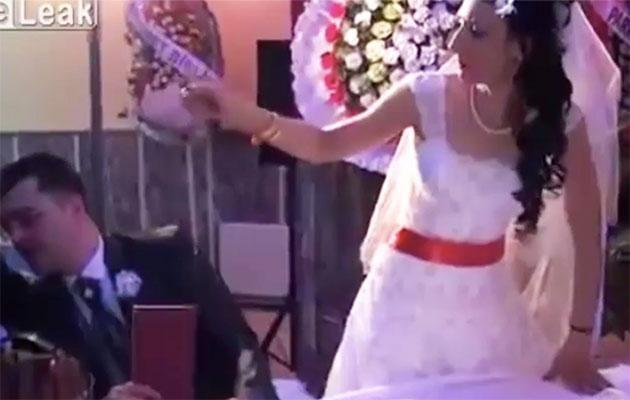 This bride hasn't noticed the chair she was sitting on has fallen over. Photo: Live Leak
