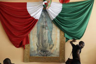 FILE - A Haitian man listening to music leans against a wall with the Mexican national flag and a framed image of the Virgin of Guadalupe, as he waits for a bed at the Padre Chava migrant shelter Monday, Sept. 26, 2016, in Tijuana, Mexico.Though Haitians living in the U.S. rejoiced when a recent extension was granted, Homeland Security Secretary Alejandro Mayorkas pointedly noted that it doesn't apply to Haitians outside the U.S. and said those who enter the country may be flown home. That means bleak choices for many Haitians who fled Haiti sometime after a 2010 earthquake, initially escaping to South America and later to Mexican cities that border the United States. (AP Photo/Gregory Bull)
