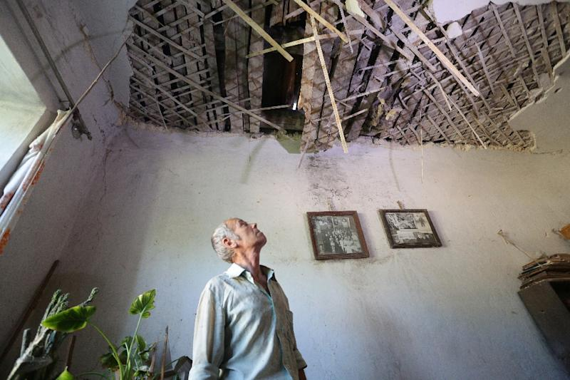 A man examines destruction in his house as a result of shelling between Ukrainian forces and pro-Russian separatists on August 10, 2015 in Golmovsky village (AFP Photo/Aleksey Filippov)