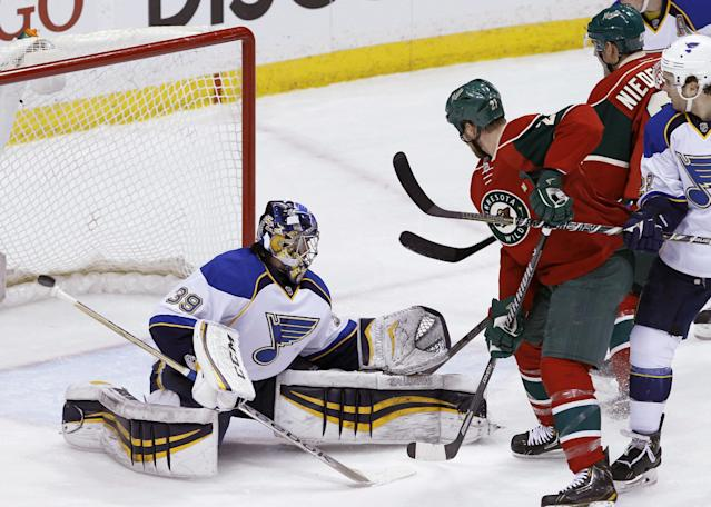 Minnesota Wild center Kyle Brodziak (21) and St. Louis Blues defenseman Kevin Shattenkirk, right, watch as a shot by Wild right wing Nino Niederreiter, rear, of Switzerland, gets past Blues goalie Ryan Miller (39) during the first period of an NHL hockey game in St. Paul, Minn., Thursday, April 10, 2014. (AP Photo/Ann Heisenfelt)