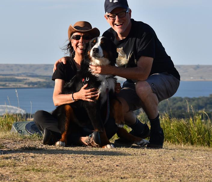 Michael Subit, his wife Leslie Hagin and dog, Breezy, are shown by South Dakota's Missouri River on their drive to New York to see Subit's parents.