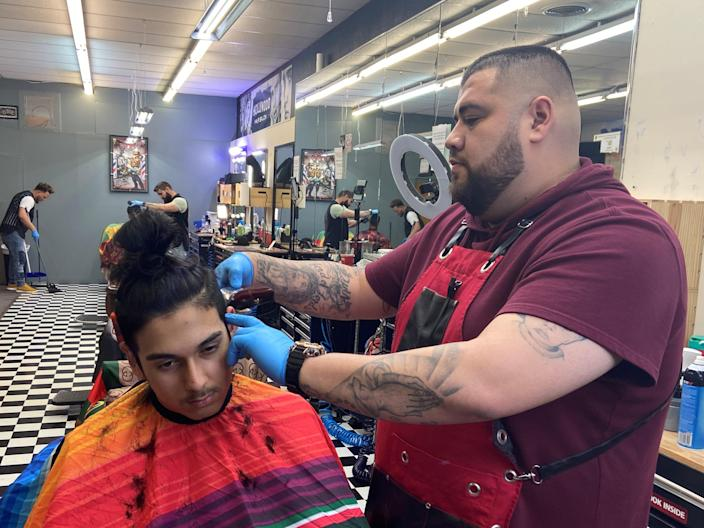 Jesus Ruiz cuts hair at Ivan Barber Studio on the Main Street in Guymon, Oklahoma, a city where local shops remain open as there has yet to be a positive case of coronavirus, in Guymon, U.S., March 26, 2020. Picture taken March 26, 2020.