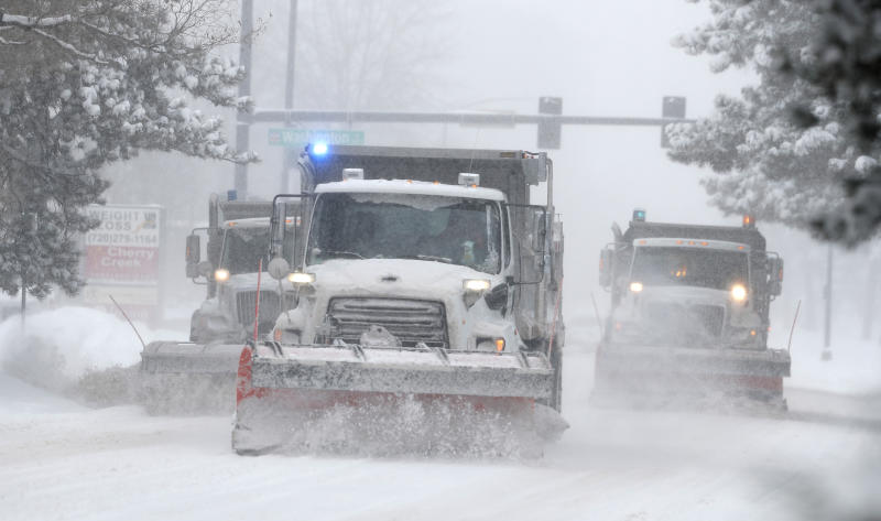 City of Denver snowplows clear the eastbound lanes of Speer Blvd. as a storm packing snow and high winds sweeps in over the region Tuesday, Nov. 26, 2019, in Denver. Stores, schools and government offices were closed or curtailed their hours while on another front, Thanksgiving Day travellers were forced to wrestle with snow-packed roads and flight delays or cancellations throughout the intermountain West. (AP Photo/David Zalubowski)