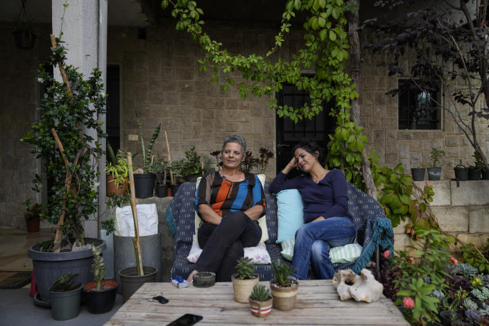 Helen Akiki, 54, left, and her daughter Saydi Mubarak, 36, both diagnosed with breast cancer, share a moment as they sit in the garden of their home, in Qleiat, Lebanon, Monday, Sept. 6, 2021. Amid a devastating economic crisis, Lebanon is grappling with severe shortages of medical supplies, fuel and other necessities, threatening treatment for tens of thousands of people. (AP Photo/Hassan Ammar)