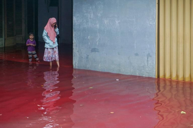 Residents waded through the blood-red floodwaters