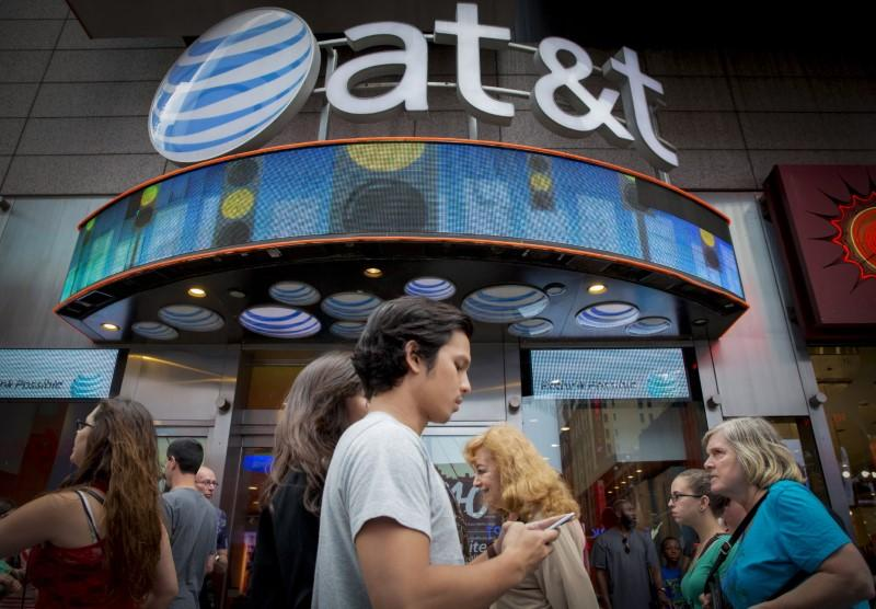 People walk past the AT&T store in New York's Times Square