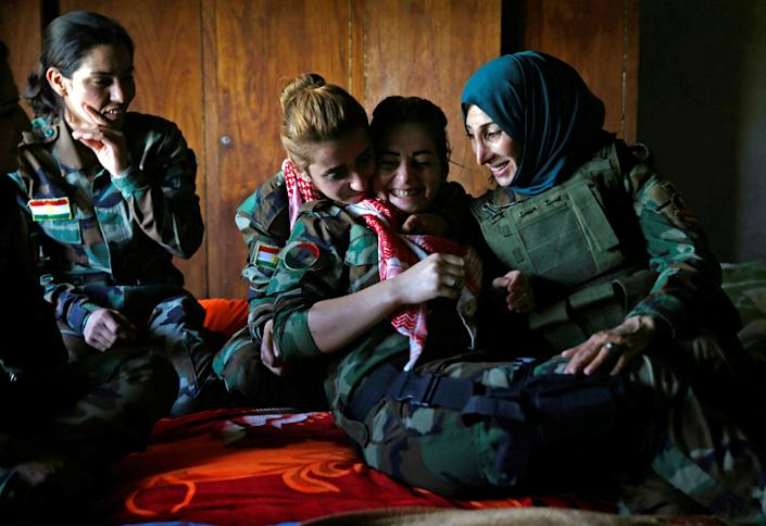 Fighters share a tender moment in a bedroom near their deployment.