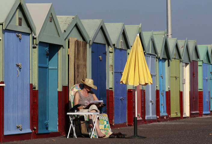 A woman reads as she sits outside a beach hut in Brighton
