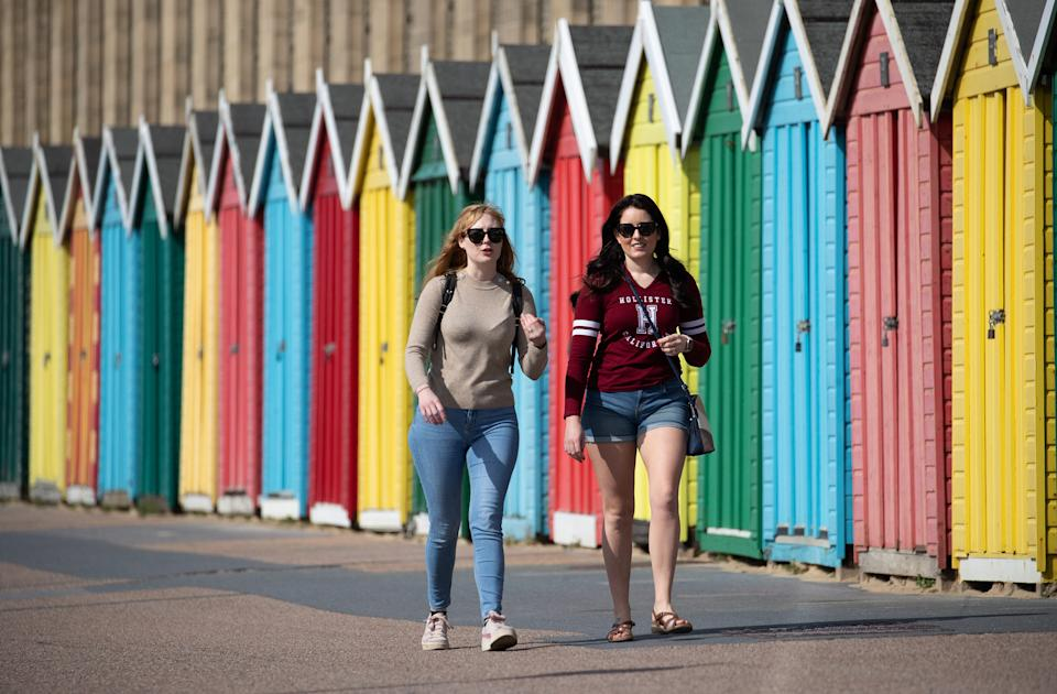 People make their way past beach huts on the sea front on Boscombe beach in Dorset. Picture date: Tuesday March 30, 2021. Temperatures in parts of the UK are expected to be significantly warmer this week as families and friends are reunited and sporting activities are allowed to resume in England.