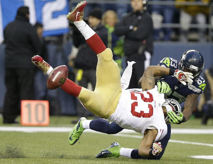 San Francisco 49ers' LaMichael James fumbles as he is hit by Seattle Seahawks' Ricardo Lockette (83) on a kick off during the first half of the NFL football NFC Championship game Sunday, Jan. 19, 2014, in Seattle. The 49ers recovered the fumble. (AP Photo/Elaine Thompson)
