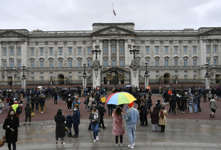 A couple under an umbrella gather with others outside the gates at Buckingham Palace in London, a day after the death of Britain's Prince Philip, Saturday, April 10, 2021. Britain's Prince Philip, the irascible and tough-minded husband of Queen Elizabeth II who spent more than seven decades supporting his wife in a role that mostly defined his life, died on Friday. (AP Photo/Alberto Pezzali)