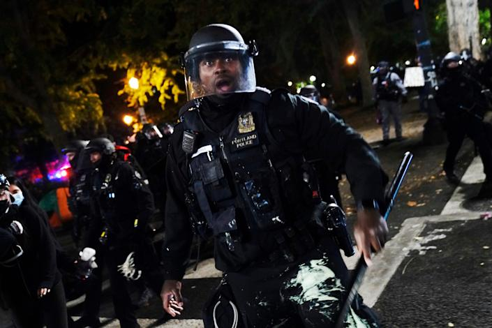 A police officer pushes back protesters Sept. 26 in Portland, Ore. The protests, which began after the death of George Floyd, have resulted in frequent clashes between protesters and law enforcement.
