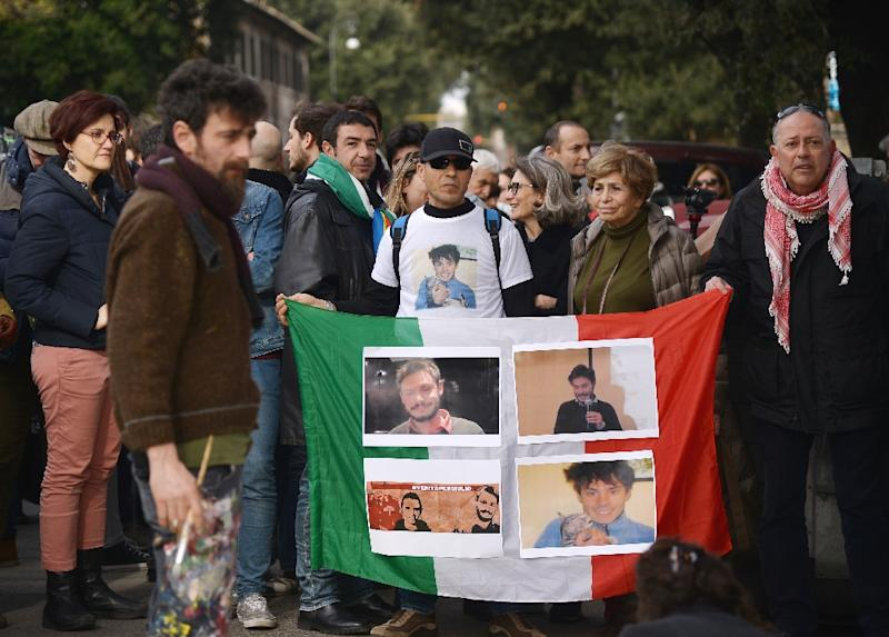 Protesters hold an Italian flag covered with photos of murdered Italian student Giulio Regeni during a demonstration in front of the Egyptian embassy in Rome on February 25, 2016