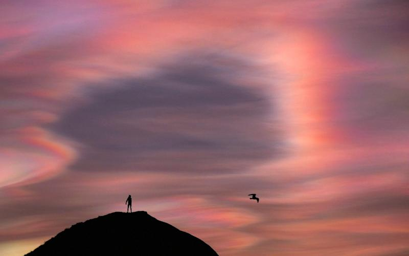 A man stands on top of a hill as ice particle iridescence is seen in high-level 'mother-of-pearl' Nacreous clouds on February 02, 2016 in Saltburn-by-the-Sea, England - Getty Images Europe