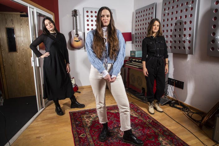 "Members of the folk group The Staves, sisters, from left, Jessica, Camilla and Emily Staveley-Taylor pose in a north London recording studio to promote their album ""Good Woman"", on Monday, Feb. 15, 2021. (Photo by Joel C Ryan/Invision/AP)"
