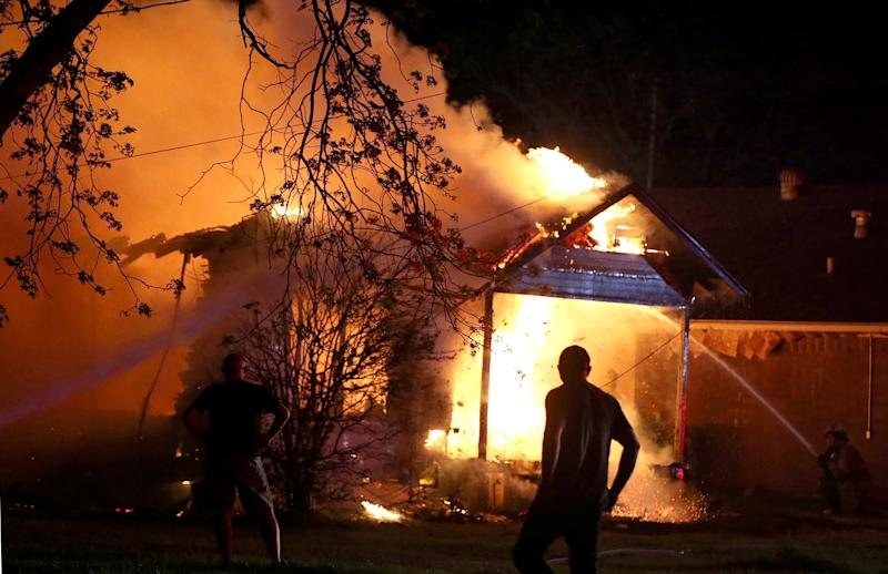 A person looks on as emergency workers fight a house fire after a near by fertilizer plant exploded Wednesday, April 17, 2013, in West, Texas. (AP Photo/ Waco Tribune Herald, Rod Aydelotte)