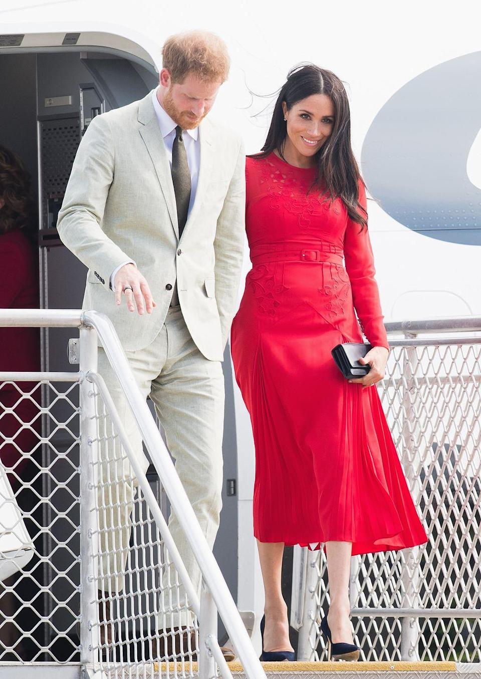 """<p>Meghan had a quick change on the plane and arrived Tonga wearing a <a href=""""https://www.townandcountrymag.com/style/fashion-trends/a24183870/meghan-markle-white-theia-gown-dinner-tonga-photo/"""" rel=""""nofollow noopener"""" target=""""_blank"""" data-ylk=""""slk:red midi-length dress"""" class=""""link rapid-noclick-resp"""">red midi-length dress</a> by Self Portrait paired with a black clutch and pumps.</p>"""