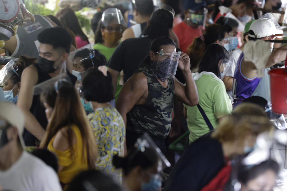 A man arranges his face shield to prevent the spread of the coronavirus at the Munoz market in Quezon city, Philippines as they prepare for a stricter lockdown on Sunday March 28, 2021. The government will start stricter lockdown measures next week as the country struggles to control an alarming surge in COVID-19 cases. (AP Photo/Aaron Favila)