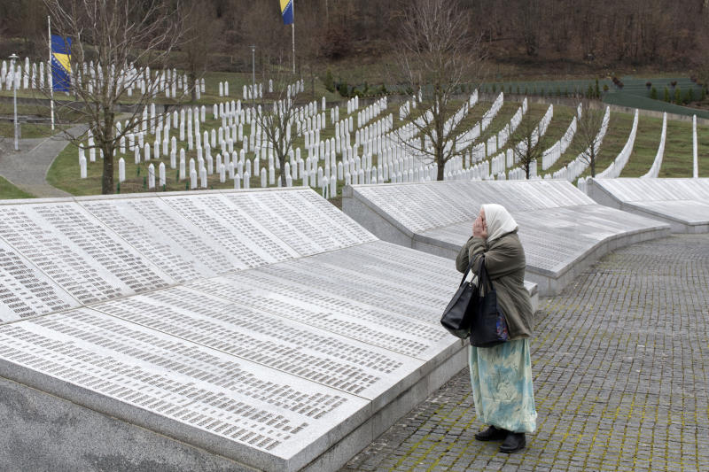 FILE - In this Wednesday, March 20, 2019 file photo, a woman prays at the Potocari memorial center for victims of the Srebrenica genocide, in Potocari, Bosnia and Herzegovina. The Dutch Supreme Court is ruling Friday July 19, 2019 in a long-running legal battle over whether the Netherlands can be held liable in the deaths of more than 300 Muslim men who were murdered by Bosnian Serb forces during the 1995 Srebrenica massacre. (AP Photo/Marko Drobnjakovic, File)