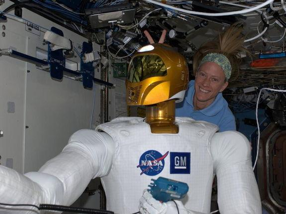 Aboard the International Space Station, astronaut Karen Nyberg indulges in a moment of levity with Robonaut 2. Image tweeted on June 28, 2013.