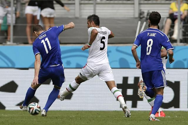 Bosnia's Edin Dzeko shoots to score his team's first goal during the group F World Cup soccer match against Iran at the Arena Fonte Nova in Salvador, Brazil, Wednesday, June 25, 2014. (AP Photo/Marcio Jose Sanchez)