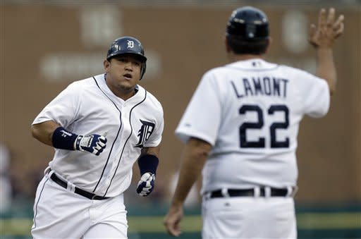 Detroit Tigers third baseman Miguel Cabrera rounds third after hitting a two-run home run as third base coach Gene Lamont celebrates during the first inning of a baseball game against he Chicago White Sox in Detroit, Friday, Aug. 31, 2012. (AP Photo/Paul Sancya)