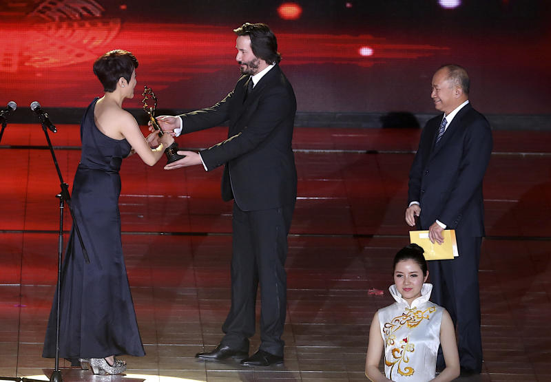 """American-Canadian actor Keanu Reeves, centre, presents the best actress award to Chinese actress Yan Bingyan, left, as Hong Kong director John Woo, right, looks on during the award ceremony for the Beijing Film Festival in Beijing Tuesday April 23, 2013. Reeves stars in his new movie """"Man of Tai Chi,"""" which also marks Reeve's directorial debut. (AP Photo) CHINA OUT"""