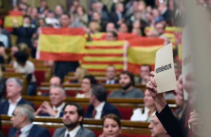 """A pro-secessionist activist holds a placard that reads """"#referendum"""" following a vote by Catalan deputies to secede from the rest of the country during a parliamentary session in Barcelona, on November 9, 2015 (AFP Photo/Lluis Gene)"""