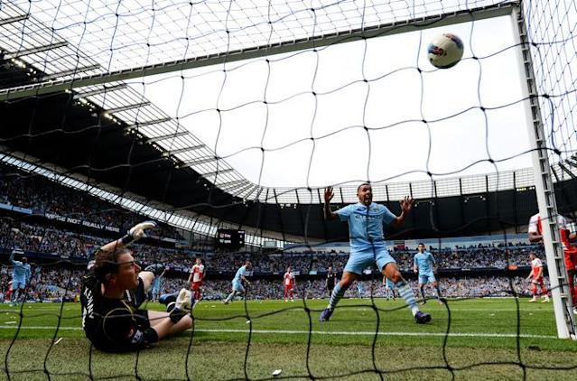 MANCHESTER, ENGLAND - MAY 13: Carlos Tevez (R) of Manchester City celebrates as the shot from teammate Pablo Zabaleta (C) beats goalkeeper Paddy Kenny (L) of QPR for the opening goal during the Barclays Premier League match between Manchester City and Queens Park Rangers at the Etihad Stadium on May 13, 2012 in Manchester, England. (Photo by Shaun Botterill/Getty Images)
