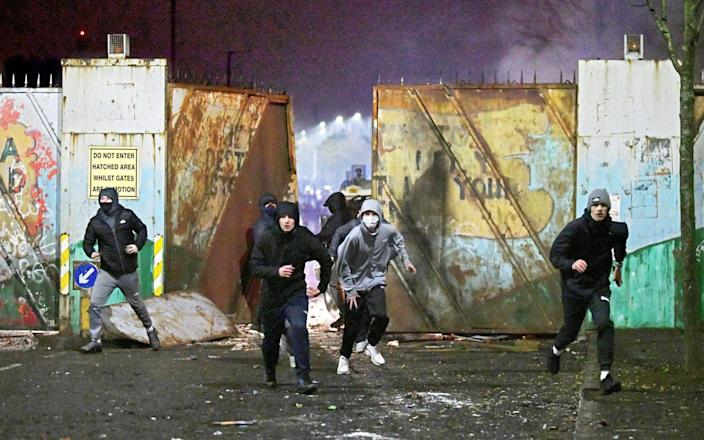 Rioters clashed outside the peace wall that divides east and west Belfast on Wednesday night, the worst night of violence so far - ALAN LEWIS/SPLASH NEWS