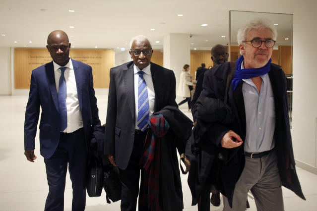 CAPTION CORRECTS SPELLING OF SURNAME Former president of the IAAF (International Association of Athletics Federations) Lamine Diack, center, arrives with his lawyer William Bourdon, right, at the Paris courthouse, Monday, Jan. 13, 2020. One of the biggest sports corruption cases to reach court is being heard in Paris from Monday, with explosive allegations of a massive doping cover-up at the top of track and field. (AP Photo/Thibault Camus)