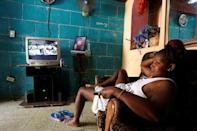 A woman rests on a sofa as the TV shows the broadcast of the National Assembly seesion, in Havana, Cuba July 21, 2018. REUTERS/ Stringer