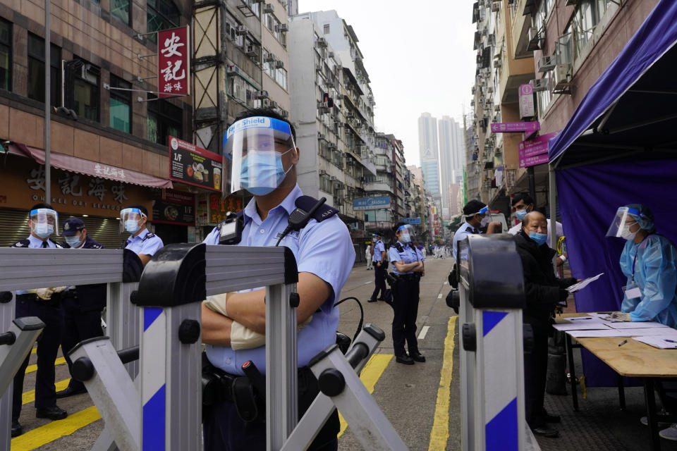 Police officers stand guard at the Yau Ma Tei area in Hong Kong, Saturday, Jan. 23, 2021. Thousands of Hong Kong residents were locked down Saturday in an unprecedented move to contain a worsening outbreak in the city, authorities said. (AP Photo/Vincent Yu)