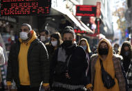 People wearing masks to help protect against the spread of coronavirus, walk in Ankara, Turkey, Friday, Nov. 27, 2020. When Turkey changed the way it reports daily COVID-19 infections, it confirmed what medical groups and opposition parties have long suspected — that the country is faced with an alarming surge of cases that is fast exhausting the Turkish health system. The official daily COVID-19 deaths have also steadily risen to record numbers in a reversal of fortune for the country that had been praised for managing to keep fatalities low. With the new data, the country jumped from being one of the least-affected countries in Europe to one of the worst-hit.(AP Photo/Burhan Ozbilici)
