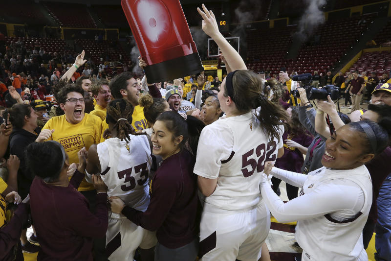 Arizona State players and students celebrate their upset win over Oregon State at the end of an NCAA college basketball game Sunday, Jan. 12, 2020, in Tempe, Ariz. (AP Photo/Darryl Webb)