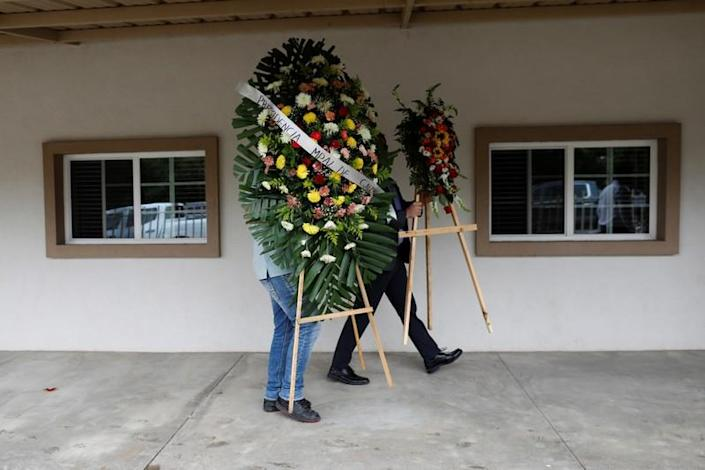 Relatives of Christina Marie Langford Johnson, who was killed by unknown assailants, arrive with flowers during the funeral service before a burial at the cemetery in LeBaron, Chihuahua